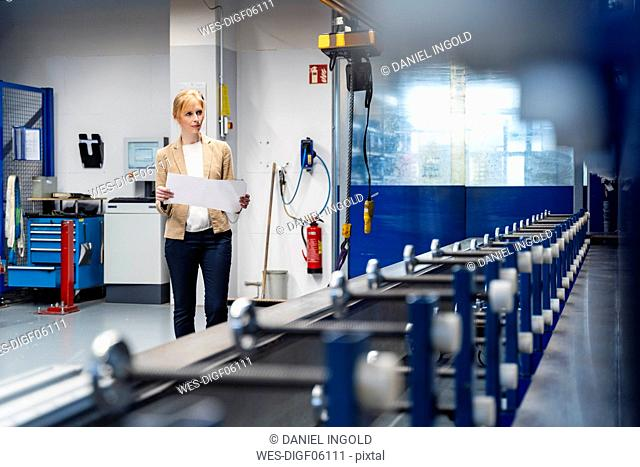 Businesswoman with plan looking at machine in factory