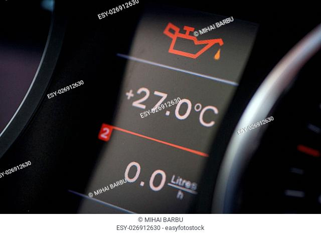 Detail of the dashboard of a car, with the oil alert icon lit up