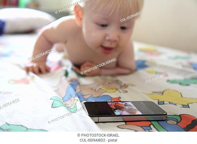 Baby plays with smartphone on bed