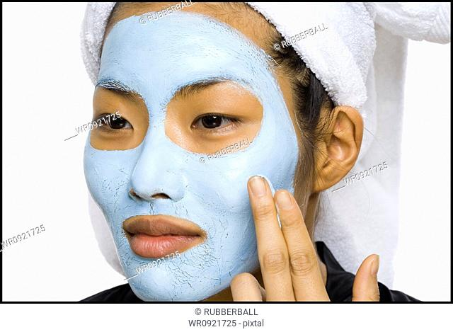 Closeup of woman applying facial mask with hair towel