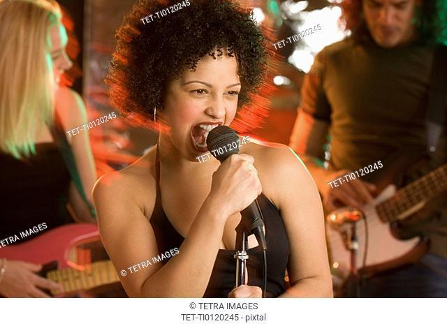 Woman singing with a band