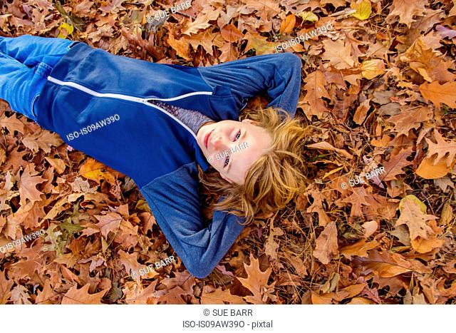 Boy lying in autumn leaves
