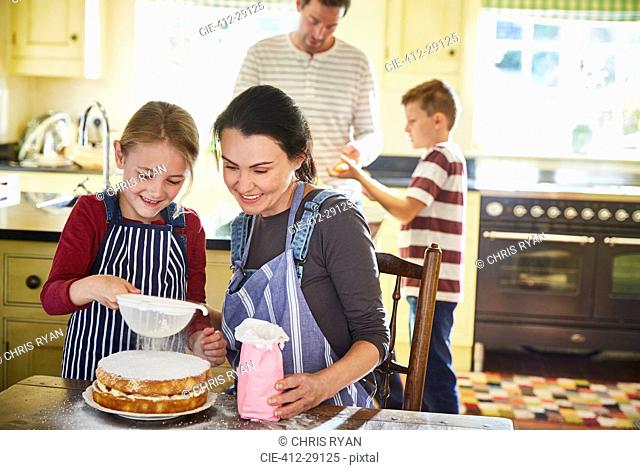Family baking cake in kitchen