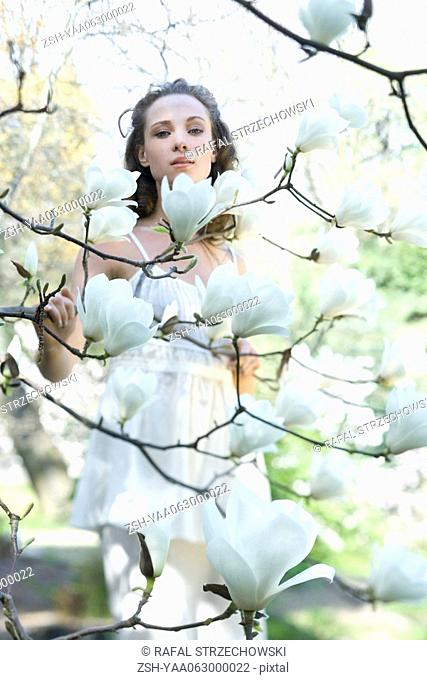 Young woman standing among flowering tree, looking at camera