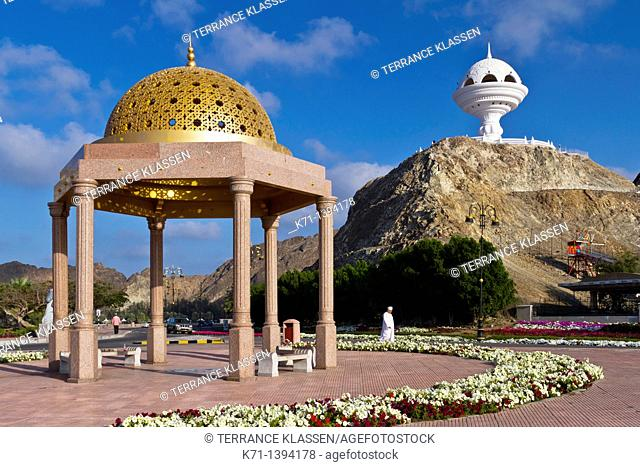 A gold dome cupola shelter and the incense burner landmark overlooking the Corniche promenade in Muscat, Oman