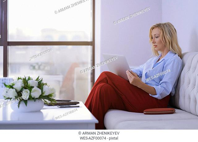 Blond woman sitting on couch, using laptop