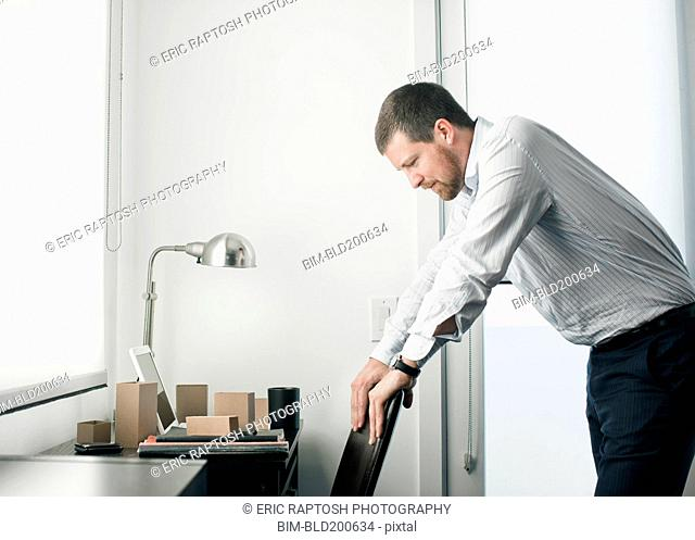Caucasian businessman leaning on chair