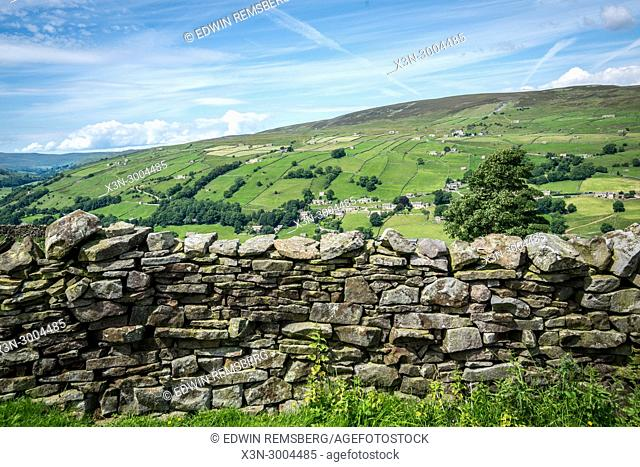 Hand built wall stands in foreground in front of rolling green hills, Yorkshire Dales, UK