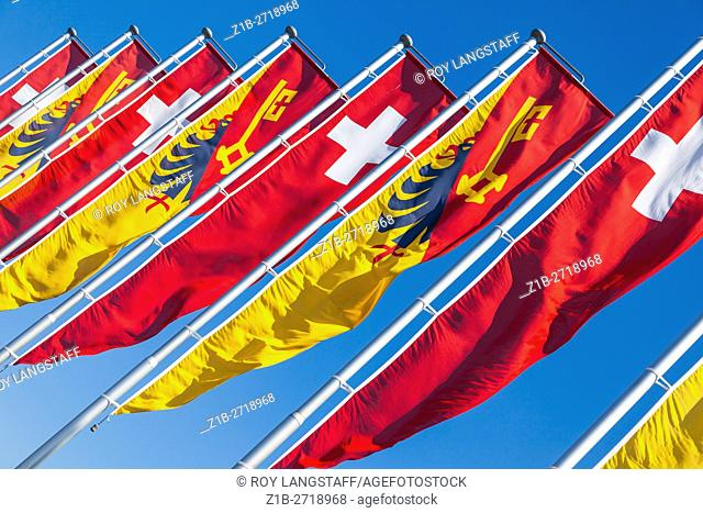 Swiss flag and Canton of Geneva banners blowing in the wind by Lake Geneva