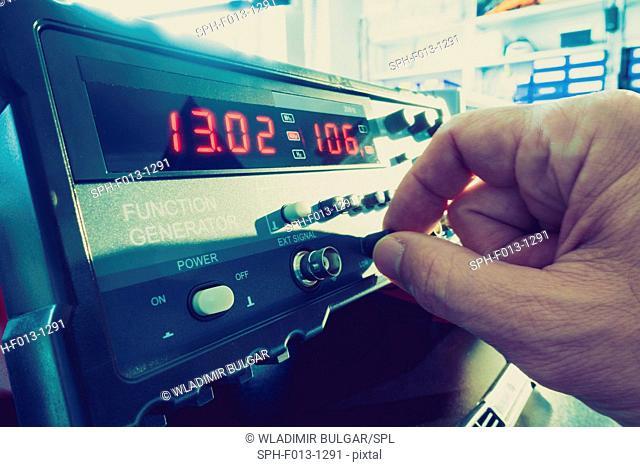 Scientist turning button on machine