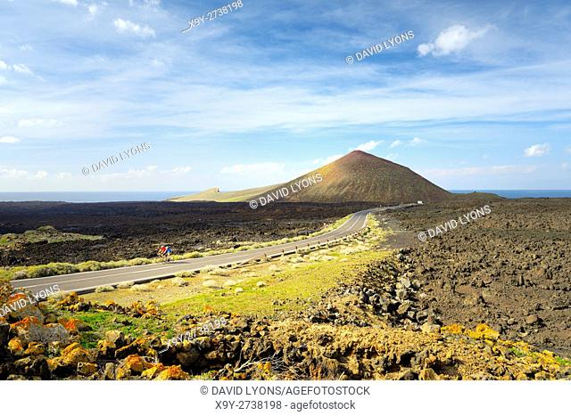 Cyclists cross lava landscape on the LZ-704 road coming from El Golfo. Timanfaya National Park, Lanzarote, Canary Islands, Spain