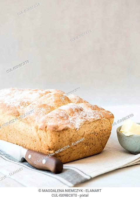 Freshly baked loaf of whole wheat bread with knife and butter