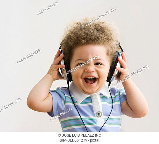 Mixed Race baby listening to headphones
