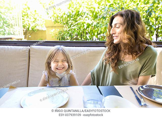 happy family sitting in restaurant: woman mother and her daughter four years old blonde girl laughing with funny face expression