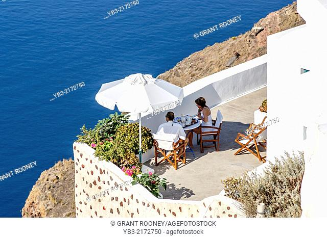 A Couple Eating Breakfast On A Terrace, Oia, Santorini, Greek Islands, Greece