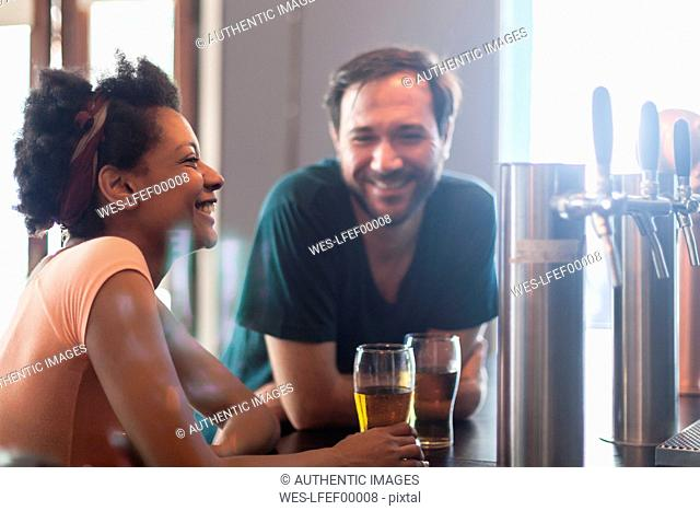 Happy couple talking and drinking beer in a bar