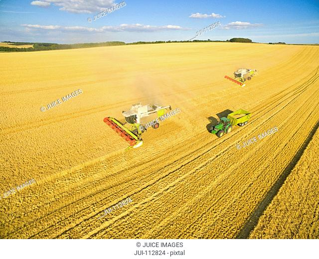 Aerial view of combine harvesters and tractor in sunny golden barley field