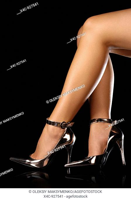 Sexy woman legs in shiny high heel shoes  Isolated on black background
