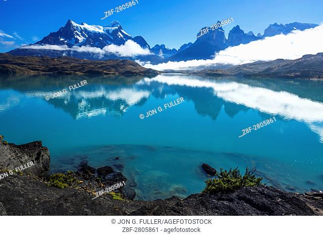 Clearing fog over Lago Pehoe. A few low clouds remain, obscuring the bases of Paine Grande and the Cuernos del Paine. The still waters of the lake provide a...