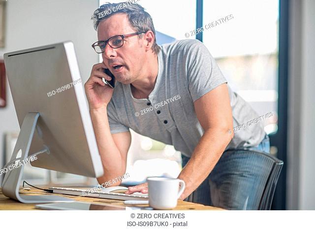 Man at computer using smartphone to make telephone call