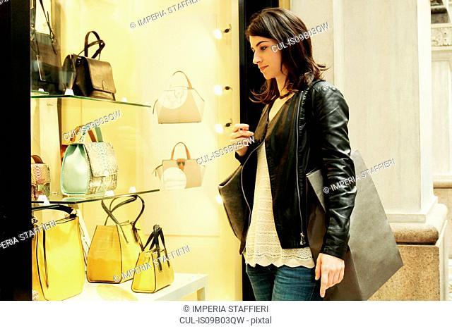 Woman looking at shop window in Galleria Vittorio Emanuele II, Milan, Italy
