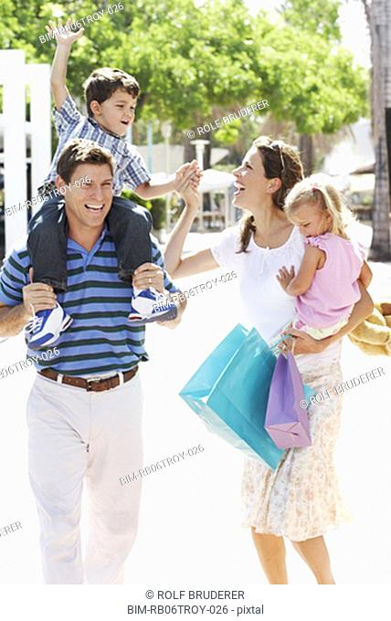 Hispanic Family Walking With Shopping Bags Outdoors