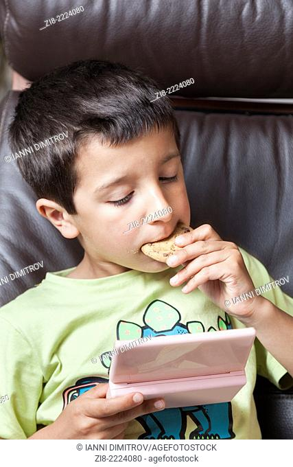 Boy plays computer games and eats biscuits