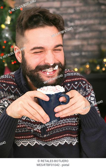 Portrait of laughing man drinking hot chocolate with whipped cream and chopped candy canes