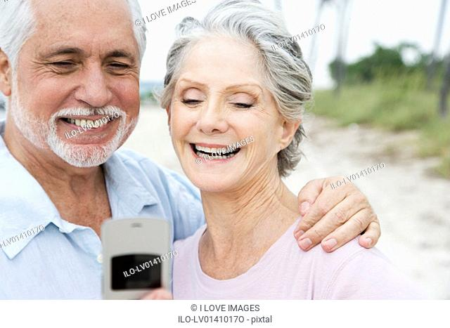 Senior couple looking at a mobile telephone at the beach