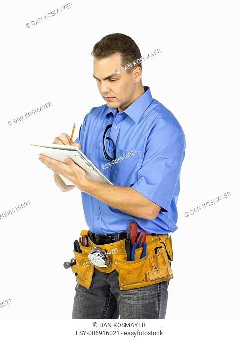 A young male construction worker writing on the notebook isolated on a white background