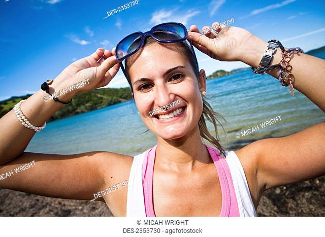 A Young Woman Poses With Sunglasses Along The Coast Of Urupukapuka Island; New Zealand