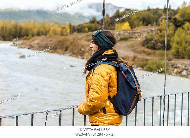 Spain, Alquezar, young woman with backpack standing on bridge