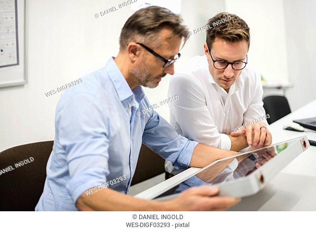 Two businessmen examining solar panel on desk in office