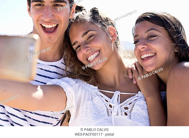Friends having fun on the beach, taking smartphone selfies