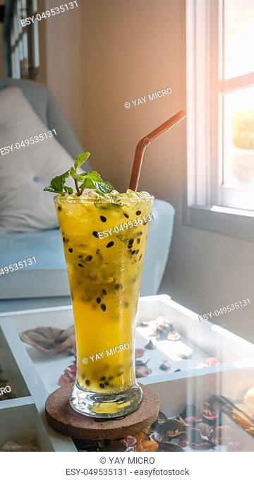 Passion fruit juice with ice cubes and drinking straws