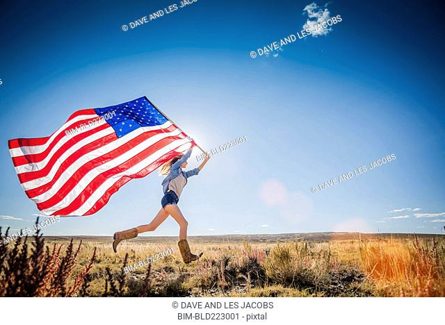 Hispanic woman running in desert carrying American flag