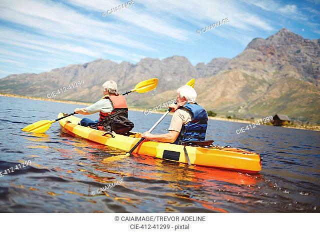 Active senior couple kayaking in sunny summer lake