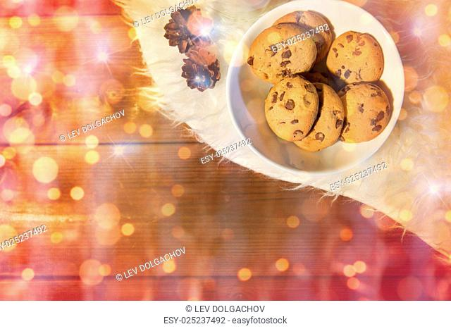 holidays, christmas, winter, advertisement and food concept - close up of cookies in bowl and cones on white fur rug over lights