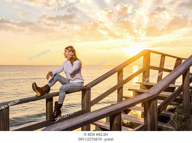 A woman sits on a wooden railing at the water's edge using a cell phone; Tarifa, Cadiz, Andalusia, Spain