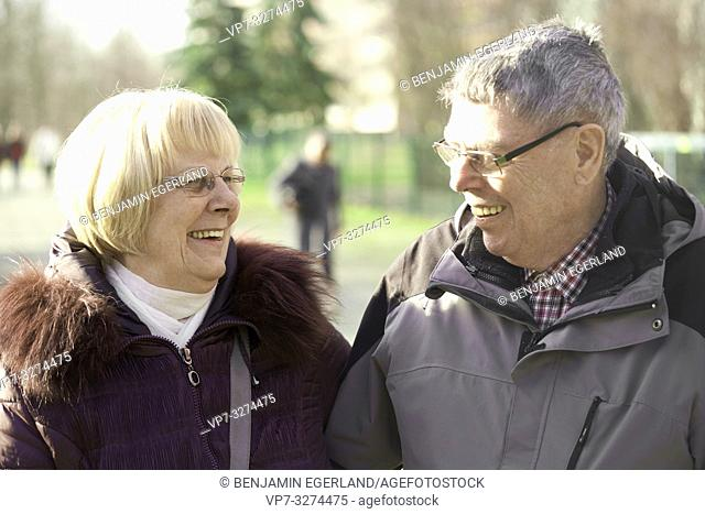 blithe senior couple together in park, looking at each other, in Cottbus, Brandenburg, Germany