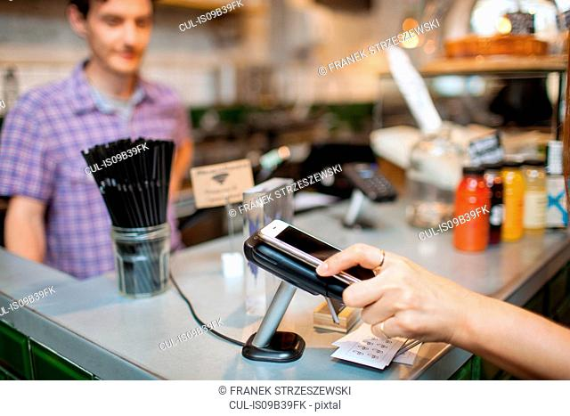 Cropped shot of female customer using smartphone contactless payment in cafe