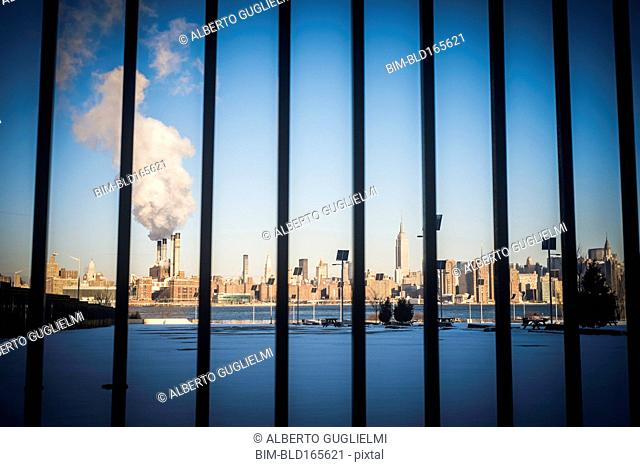 Bars in front of smokestack in city skyline, New York, New York, United States
