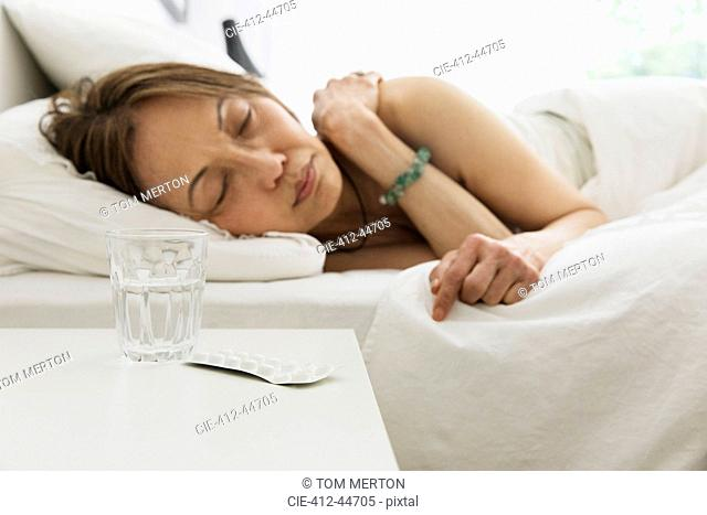 Senior woman sleeping in bed with water and medicine on night stand