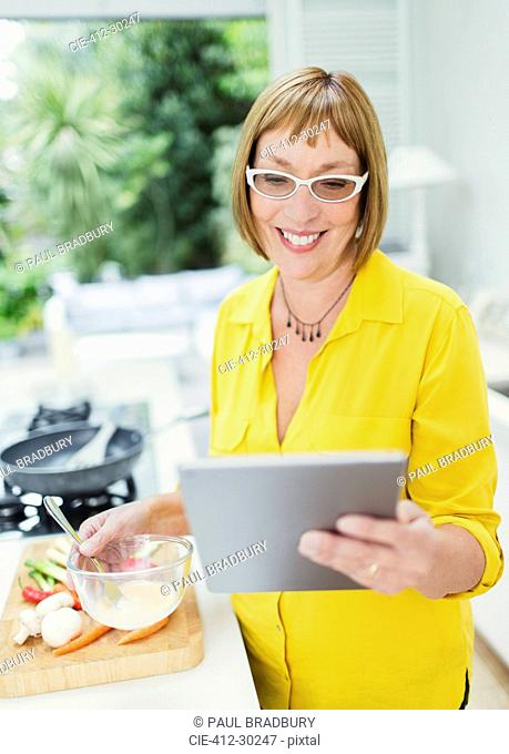 Smiling mature woman using digital tablet and cooking in kitchen