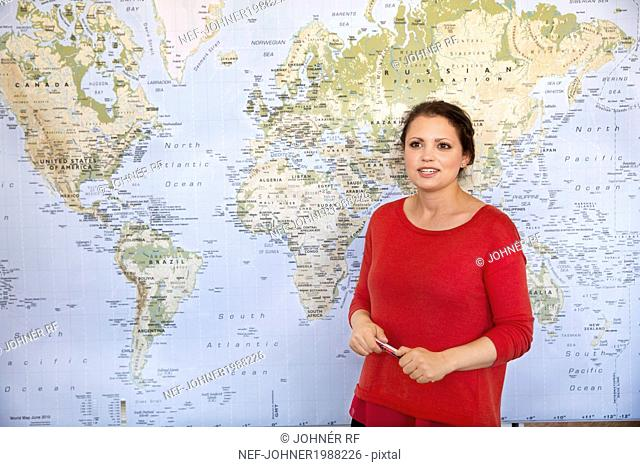 Smiling woman in front of world map