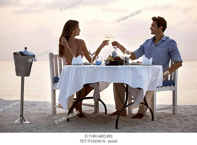 Couple eating at table on tropical beach