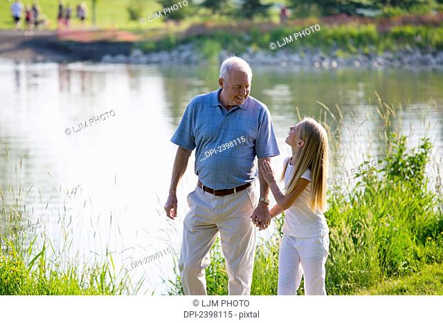 Grandfather and granddaughter spending quality time together in a park; Edmonton, Albert, Canada