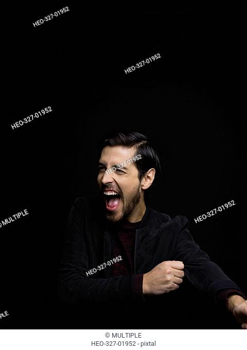 Portrait exuberant brunette man with beard laughing and looking away against black background