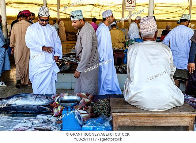 Omani Men In Traditional Dress Buying Fish At The Fish Market, Muttrah, Muscat, Sultanate Of Oman