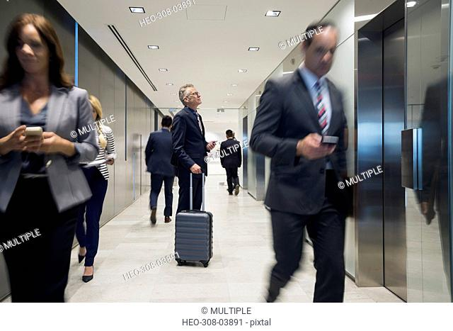 Businessman with luggage waiting for elevator in corridor
